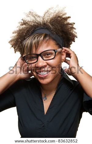 Young African girl fixes her hair band while smiling in front of a white background. - stock photo