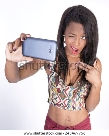 Young African girl taking a photo with smart phone - stock photo