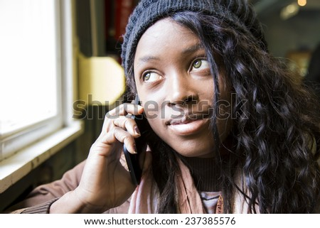 Young african girl talking on phone - stock photo