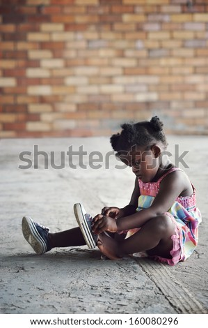 Young african girl tying shoelace and putting shoot on foot in rural setting - stock photo