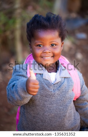 young african girl with a positive thumb up on her way to school in a pink bag and gray school clothes - stock photo