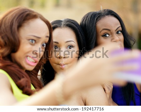 young african girls making silly faces and taking pictures of themselves - stock photo