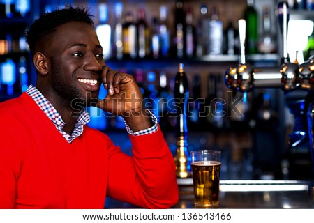 Young african guy with beer glass beside him looking at something and smiling.