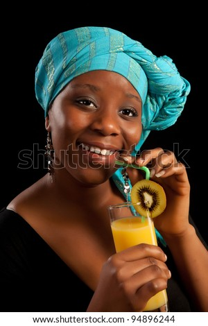 Young African lady drinking orange juice and wearing traditional ghanese scarf - stock photo