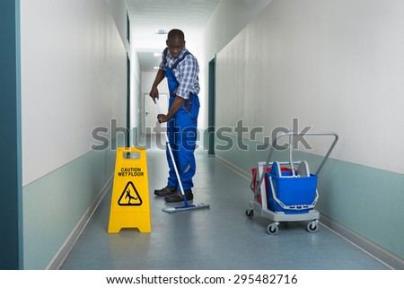 Young African Male Janitor Cleaning Floor In Corridor - stock photo