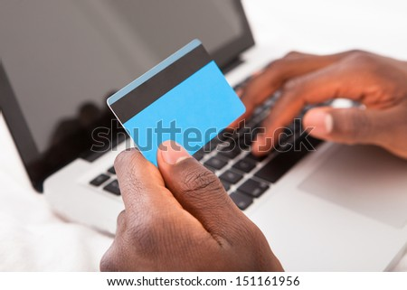 Young African Man Holding Credit Card And Using Laptop For Online Shopping