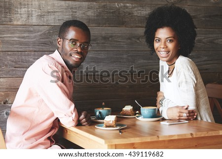 Young African office worker in glasses having lunch with his fashionable female colleague with Afro hairstyle and braces, looking and smiling at the camera while having a nice conversation at a cafe - stock photo