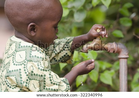 Young African school boy holding hands under a tap. Water scarcity problems concern the inadequate access to safe drinking water. 1 billion people in the developing world don't have access to it. - stock photo