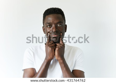Young African student in casual clothes, looking at the camera with sad tired expression on his face, making himself smile by stretching the corners on his mouth, pretending to look cheerful - stock photo