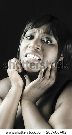 Young African woman acting as someone in pain or sad - stock photo