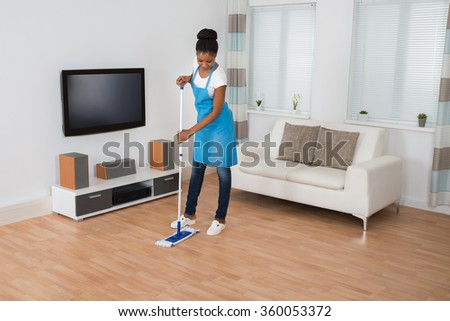 Young African Woman Cleaning Living Room With Mop