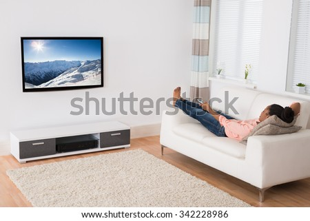 Young African Woman Lying On Sofa Watching Television - stock photo