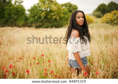 Young african woman picking poppys - stock photo