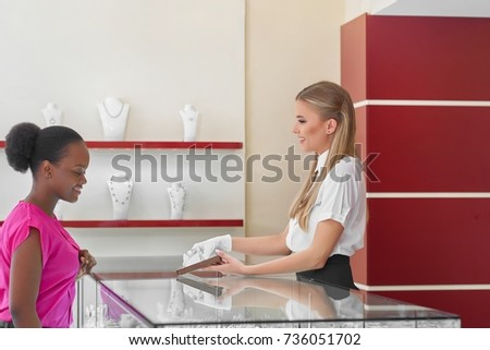 Young African woman shopping at the jewelry store talking to a professional jeweler asking for advice.