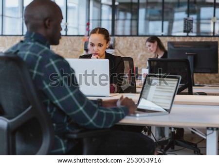 Young african woman sitting at her desk working on laptop computer. Businesswoman looking at laptop screen. - stock photo