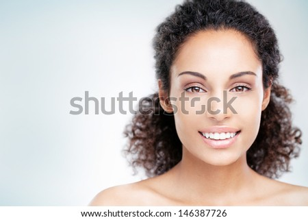 Young African woman smiling and posing in front of a blue background. - stock photo