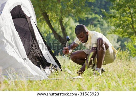 Young afro-american man fastening tent and holding hammer - stock photo