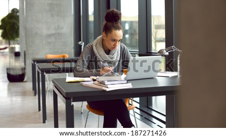 Young afro american woman sitting at table with books and laptop for finding information. Young student taking notes from laptop and books for her study in library. - stock photo
