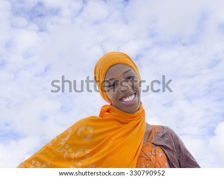 Young Afro beauty wearing a traditional headscarf in the street  - stock photo