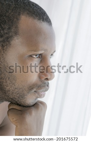Young Afro man concerned, side view - stock photo