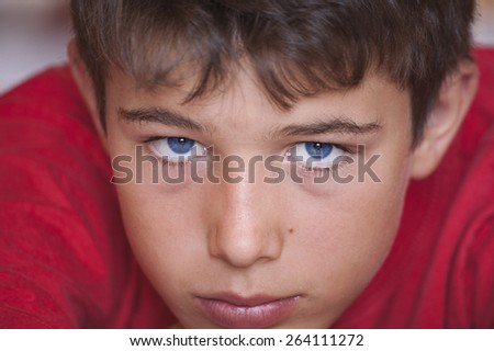 Young, aged twelve, looking seriously at the camera - stock photo