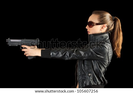 Young agent with gun isilated on black background - stock photo