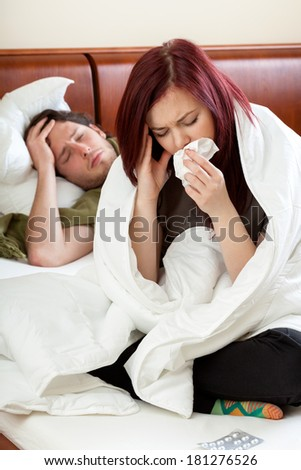 Young ailing couple in their bedroom, vertical - stock photo