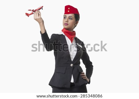 Young airhostess looking at toy airplane isolated over white background - stock photo