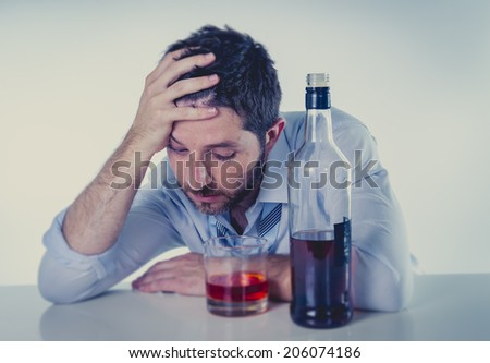 young alcoholic business man with beard looking wasted suffering hangover wearing blue shirt and tie drunk and drinking  Scotch or Whisky on office desk at work cool color edit - stock photo