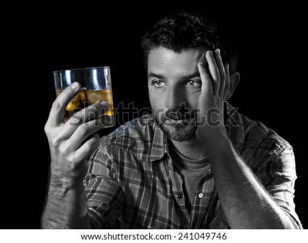 young alcoholic wasted man drunk looking at whiskey glass thinking and feeling temptation to drink in alcohol addiction and alcoholism concept isolated on black - stock photo