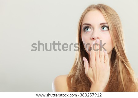 Young amazed woman covering her mouth with hand looking upwards on gray