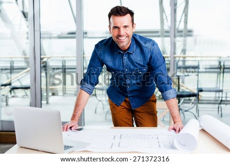 Young ambitious architect presenting the blueprint of a new house - stock photo