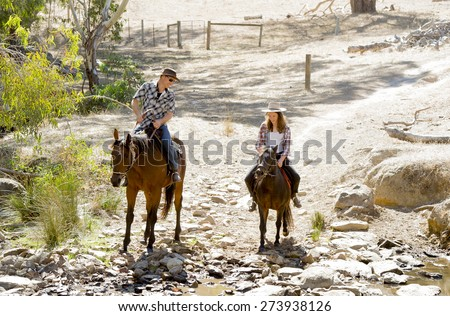 young American Australian man as father or horse instructor of young girl or  teen daughter riding little pony wearing cowgirl hat in countryside Summer vacation ride  - stock photo