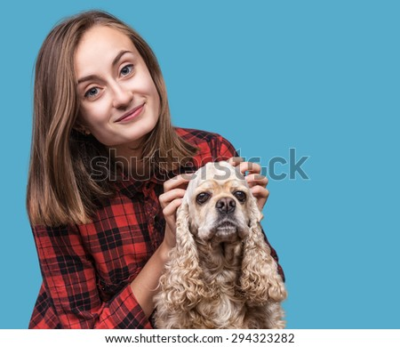 Young american cocker spaniel and beautiful woman on blue background with copyspace