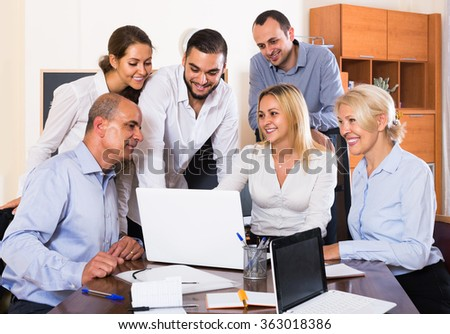 young american colleagues looking at laptop and smiling