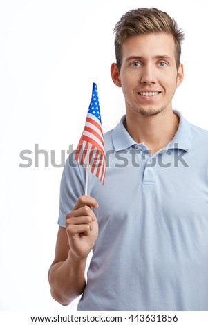 Young American patriot guy celebrating 4th of July holiday with flag of United States in hand. Attractive young male model with toothy smile isolated on white
