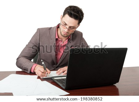 Young and and handsome business man signing new contracts in his office at his desk while the laptop is also open. He has a white wall behind him.