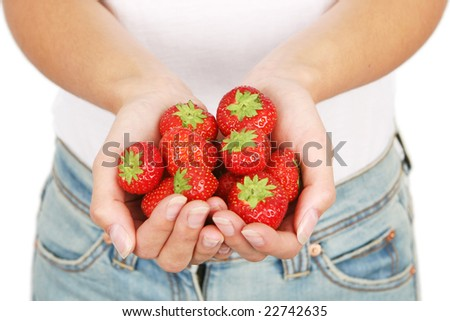 Young and attractive girl holding strawberries. Isolated on white. Shallow DOF, focus on strawberries. - stock photo