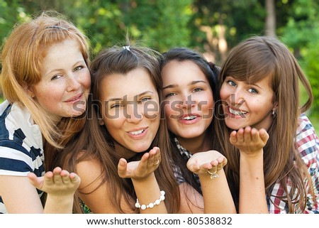 Young and attractive girlfriends have fun in park - stock photo