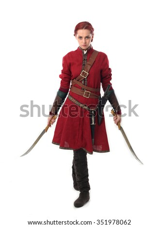 young and attractive red haired  female warrior,  wearing a red medieval tunic and leather Armour. holding swords as weapons, walking towards camera. isolated on a white background. - stock photo