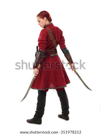 young and attractive red haired  female warrior,  wearing a red medieval tunic and leather Armour.  holding swords as weapons. back view.isolated on a white background. - stock photo