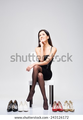 Young and attractive woman choosing shoes over grey background - stock photo