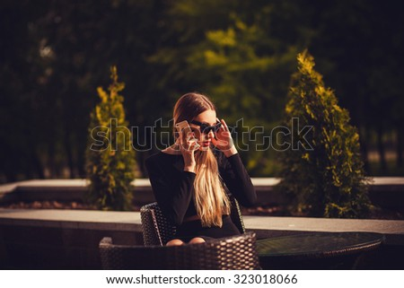 young and attractive woman on the phone sitting in a cafe. copyspace - stock photo