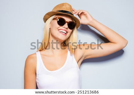 Young and beautiful. Beautiful young blond hair women adjusting her hat and smiling while standing against grey background   - stock photo
