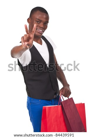 young and beautiful black man holding shopping bags and doing victory sign - stock photo