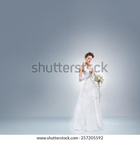 Young and beautiful bride in a long fantasy dress standing with a flower bouquet over the grey background. - stock photo