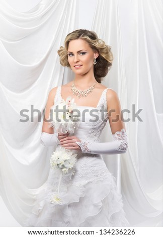 Young and beautiful bride standing with the flower bouquet over the grey background - stock photo