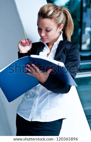 young and beautiful business woman exploring documents in a blue folder - stock photo
