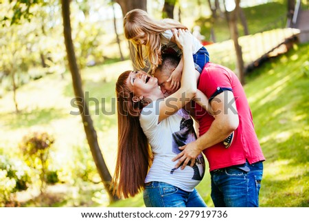 Young and beautiful family in the park, a pregnant mother, father, daughter