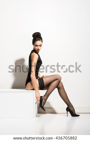 Young and beautiful fashion model posing in stockings and lingerie over white background - stock photo